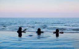人头剪影在游泳池overlooki边缘的  库存图片