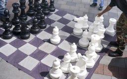 人移动演奏巨型下棋比赛边路Downtow的片断人 图库摄影