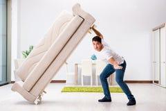 年轻人移动的家具在家 库存照片