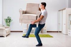 年轻人移动的家具在家 免版税库存照片