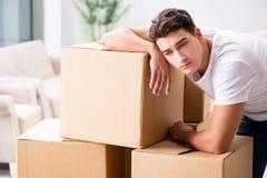 年轻人移动的箱子在家 免版税库存图片