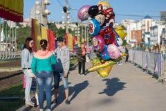 人们卖有氦气的气球在保护孩子,海湾,市的底部切博克萨雷,楚瓦什人共和国, R 免版税图库摄影