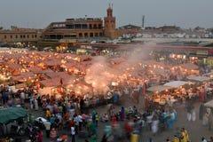 人们参观Jemaa el Fna广场在日落 免版税库存图片