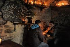 人们吃与中世纪小酒馆 免版税库存图片