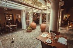 人们吃在豪华餐馆里面的晚餐在减速火箭的印地安样式 库存图片
