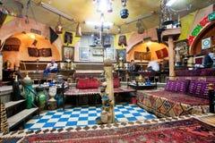 人们吃晚餐在有老地毯、葡萄酒家具和艺术的咖啡馆房子 库存照片