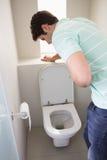 人以呕吐的胃憔悴入洗手间 免版税库存照片