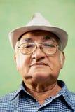 严肃的老人画象有看照相机的帽子的 免版税库存图片