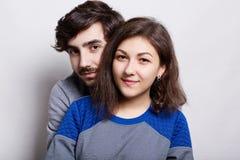 人们和关系 站立在白色墙壁附近的年轻夫妇 有站立的胡子的一个行家人behing他的拥抱h的女朋友 免版税库存图片