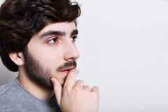 人们和情感 年轻人困惑了灰色毛线衣的时兴的学生认为事重要,抚摸或者接触他的 图库摄影