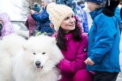 人们和狗在冬天名字的结尾的庆祝时 图库摄影