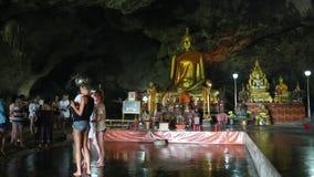 人们和金黄菩萨雕象在寺庙在洞,泰国里面 影视素材