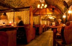 人们喝在与木桌的老酒吧里面 免版税库存图片