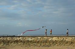 人们在一个大风天设法飞行一只风筝在努沙Dua海滩 免版税库存照片