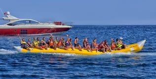 人们在一条可膨胀的小船乘坐入海 免版税库存图片