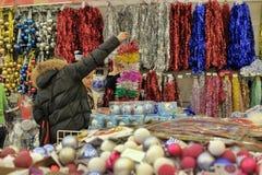 人们在买圣诞节装饰的商店 免版税库存图片