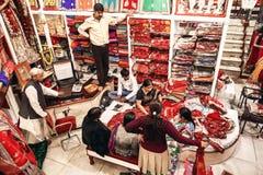 人们在传统印地安莎丽服地方纺织品商店  库存照片