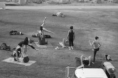 人们在做瑜伽的海滩的公园 免版税库存图片