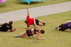 人们在健身新兵训练所的草解决 库存图片