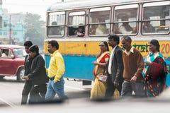 人们在加尔各答,印度穿过有许多汽车的路 库存图片