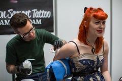人们在国会商展中心做纹身花刺在第10次国际纹身花刺大会 免版税库存图片