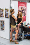 人们在国会商展中心做纹身花刺在第10次国际纹身花刺大会 免版税库存照片