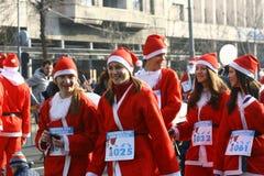 人们在圣诞老人服装在种族参与 免版税库存照片