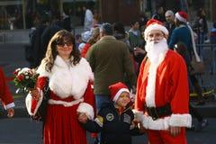 人们在圣诞老人服装在种族参与 库存照片