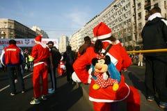 人们在圣诞老人服装在种族参与 图库摄影