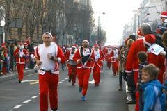 人们在圣诞老人服装在种族参与 库存图片