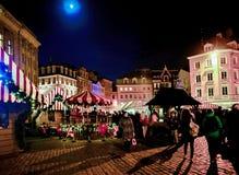 人们在圣诞节市场上在里加在晚上 免版税库存照片