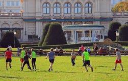 人们在城市公园演奏飞碟 库存图片