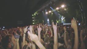 人们在夜总会摇摆在生活摇滚乐音乐会的手 执行在阶段的带 歌手,吉他弹奏者 股票录像