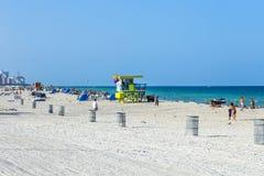人们在救生员塔旁边享用海滩 免版税图库摄影