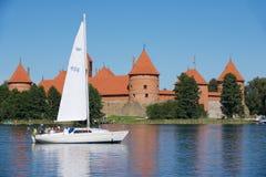 人们在有特拉凯城堡的Galve湖享受小船旅行在背景在一个热的夏日在特拉凯,立陶宛 库存图片
