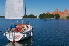 人们在有特拉凯城堡的Galve湖享受小船旅行在背景在一个热的夏日在特拉凯,立陶宛 图库摄影