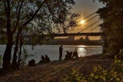 人们在河岸放松在日落 免版税库存照片
