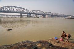 人们在河恒河洗浴靠近非常的桥梁 免版税库存图片
