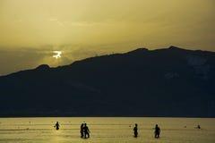 人们在海沐浴在日出 免版税库存照片