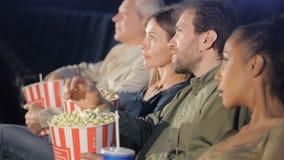人们在电影院在他们的手上拿着桶用玉米花 股票录像