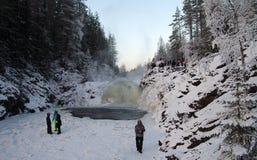 人们在背景瀑布Kivach被拍摄在多云1月天 卡累利阿,俄罗斯 免版税图库摄影
