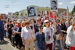 人们在胜利天拿着他们的行动`不朽的军团`的亲戚画象在伏尔加格勒 库存图片
