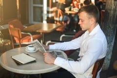 人读在街道咖啡馆的一张报纸在午餐 库存图片