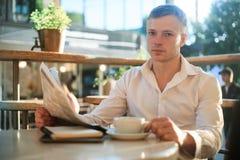 人读在街道咖啡馆的一张报纸在看照相机的午餐 免版税库存照片