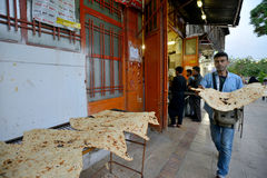 人们在设拉子,伊朗在一个市场上换面包 免版税库存图片