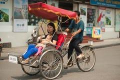 人们在采取出租机动三轮车乘驾的区域在河内,越南 免版税库存照片