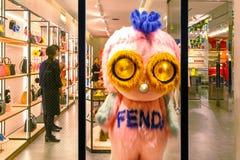 人们在银座区装饰在芬迪精品店前面的一个动画片吉祥人 图库摄影