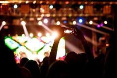 人们在音乐会做与他的智能手机的照片 免版税库存照片