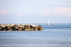 人们在风平浪静的一条风船航行 免版税图库摄影