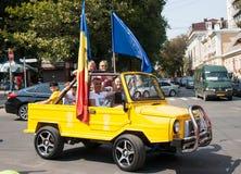 人们在黄色汽车高兴垂悬与在摩尔多瓦共和国的美国独立日的旗子 免版税库存照片